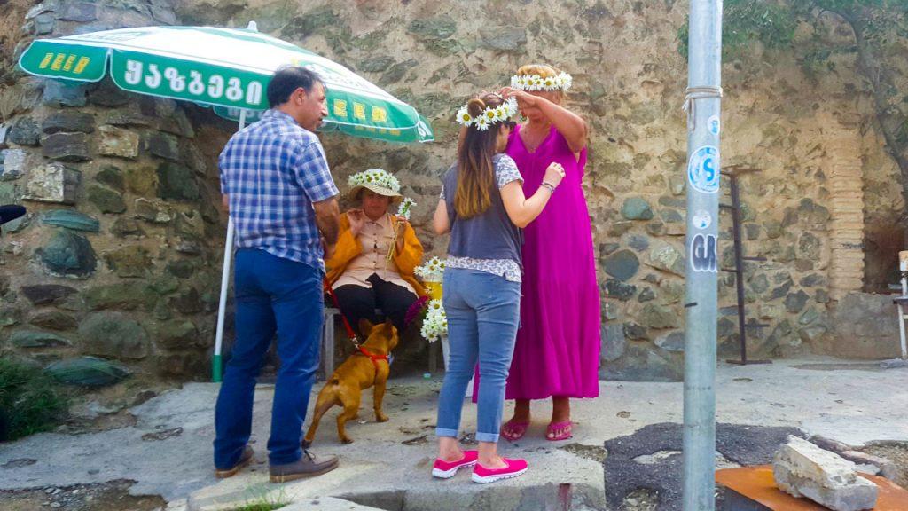 سيدتان تبيعان إكليل من زهرة الأقحوان عند مدخل المحمية النباتية
